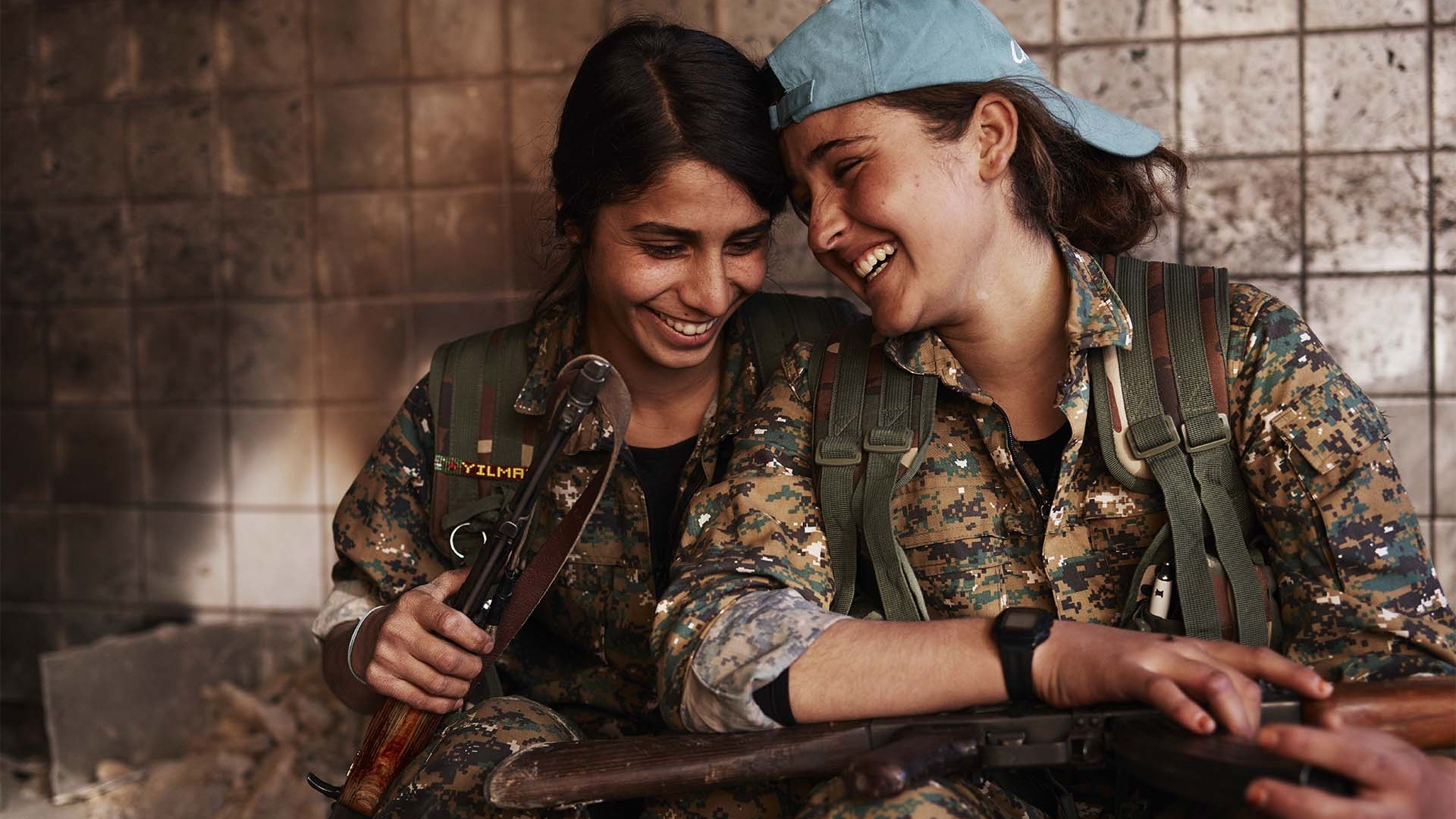 Silava and Berivan share a laugh in an abandoned ISIS base
