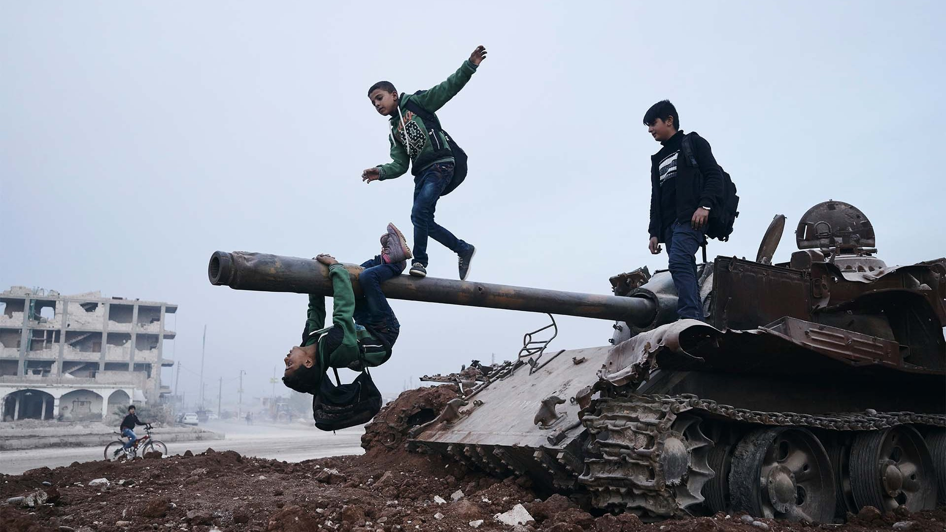 Amude, Memo, and Salar play on a destroyed ISIS tank after school