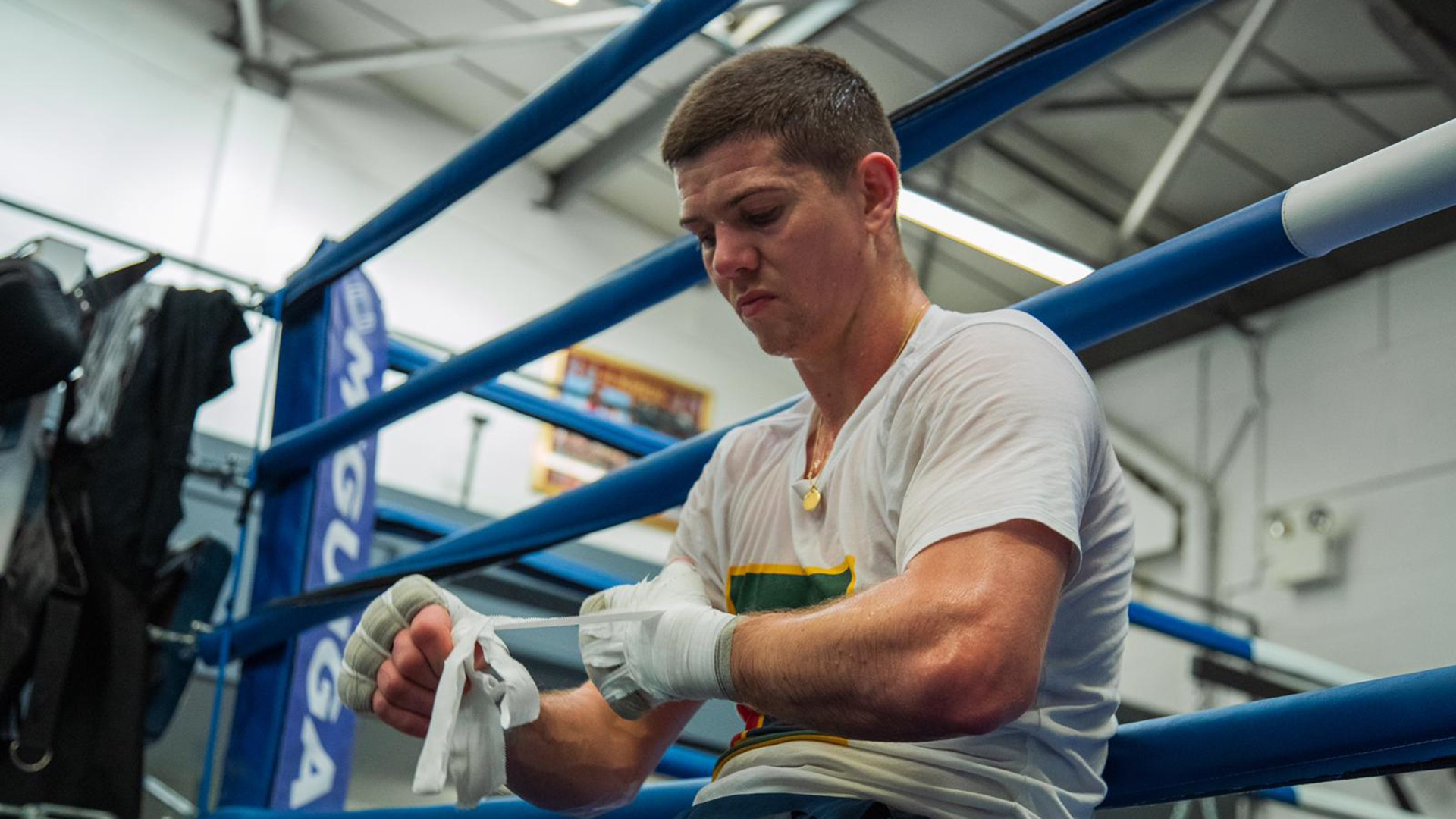Luke Campbell strapping boxing glove in gym